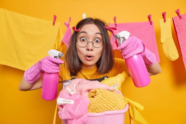 Zszokowana, zajęta azjatycka gospodyni domowa ma ciemne włosy, która jest pod wrażeniem kamery trzyma dwie butelki z dozownikami zaangażowane w sprzątanie domu myje pranie w pobliżu kosza pełnego nieporządnych przedmiotów z detergentami