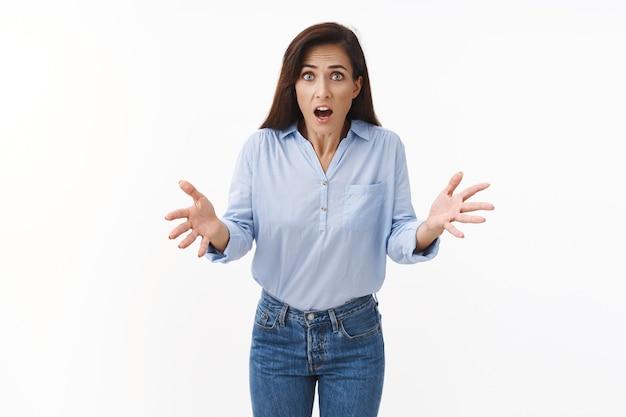 Zszokowana zaniepokojona dorosła kobieta brunetka, podnoszące ręce wyglądają na zaniepokojonych, panikujących, wyjaśniają okropną sytuację, czują się zdziwione, potrząsają spojrzeniem z przodu, stoją zachwycone białą ścianą