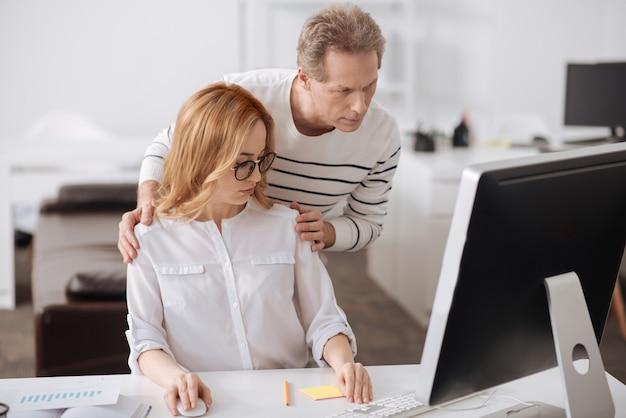 Zszokowana, zaskoczona młoda sekretarka siedząca w biurze i pracująca nad projektem wyrażająca oburzenie zachowaniem szefa