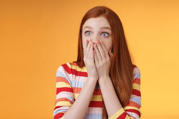 Zszokowana zdenerwowana ruda kobieta świadek strasznego wypadku sapiąca zakrywająca usta dłonie zdziwiona wpatrując się w lewo przestraszona wyrazić empatię zmartwienie stojąc pomarańczowe tło panikujące. skopiuj miejsce
