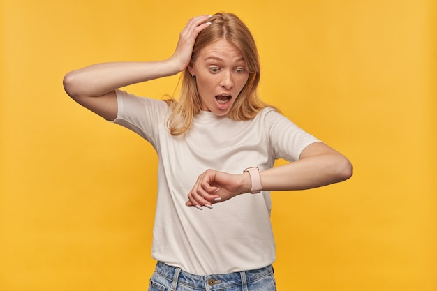 Zszokowana zdumiona kobieta z piegami w białej koszulce wygląda na zdumioną i patrzy na inteligentny zegarek na żółtym tle
