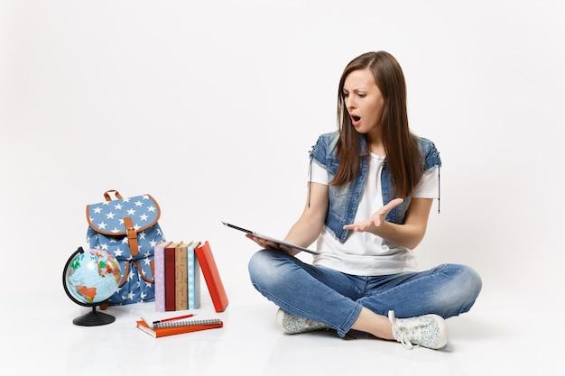 Zszokowana zirytowana studentka trzymająca się za pomocą komputera typu tablet pc, rozkładająca rękę, siedząca w pobliżu kuli ziemskiej, plecaka, podręczników szkolnych na białym tle