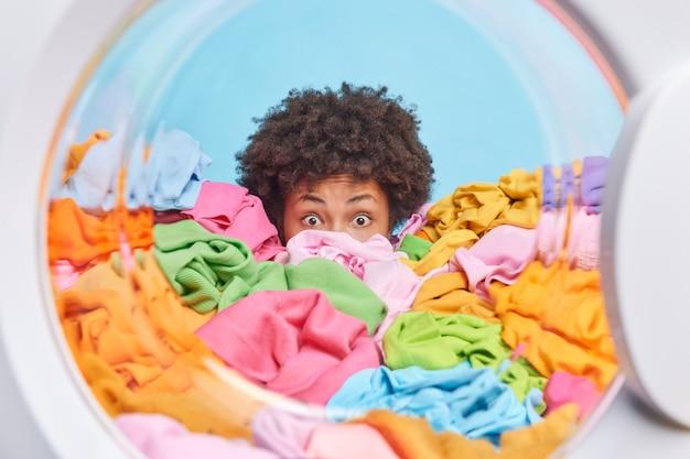 Zszokowana, zmartwiona kobieta chowa się za wielką stertą prania przeładowaną pracami domowymi i obowiązkami domowymi, wpatruje się wyłupiastymi oczami w pozy z bębna pralki