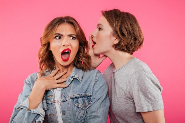 Zszokowane dwie kobiety plotkują.