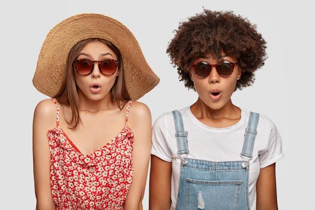 Zszokowane i pełne emocji kobiety podróżują latem po miejscowości wypoczynkowej, noszą modne okulary przeciwsłoneczne, sukienki