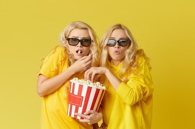 Zszokowane młode modelki kobiety w okularach 3d jedzące popcorn, wyglądają przerażająco film. pojedynczo na żółtej ścianie