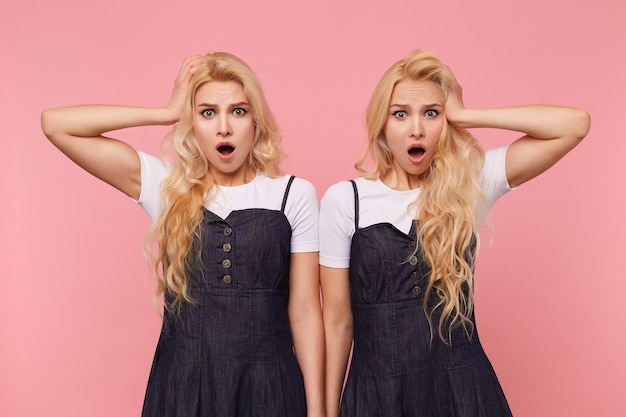 Zszokowane młode urocze, długowłose blondynki kobiety trzymające podniesione dłonie na głowach, patrząc oszołomiony na aparat z szeroko otwartymi ustami, odizolowane na różowym tle