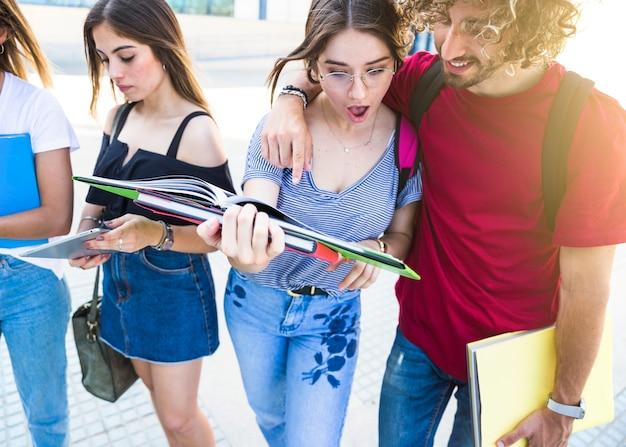 Zszokowani studenci czytać podręcznik w pobliżu przyjaciół