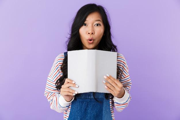 Zszokowany asian kobieta pozowanie na białym tle nad fioletową ścianą trzymając książkę