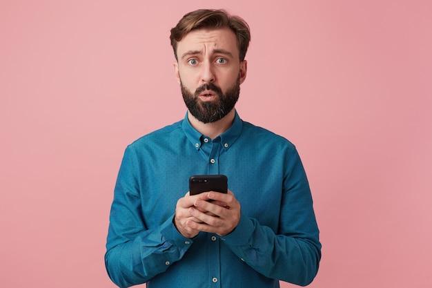 Zszokowany atrakcyjny brodaty mężczyzna, patrząc na aparat z otwartymi ustami, zdenerwowany, ubrany w dżinsową koszulę, trzymając smartfon w dłoniach, patrząc na aparat odizolowany na różowym tle.