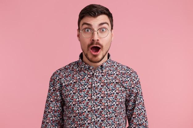 Zszokowany atrakcyjny ciemnowłosy przystojny młody mężczyzna wpatrujący się w okulary, nieogolony z brodą i wąsami w kolorowej koszuli otworzył usta z zaskoczenia, odizolowany