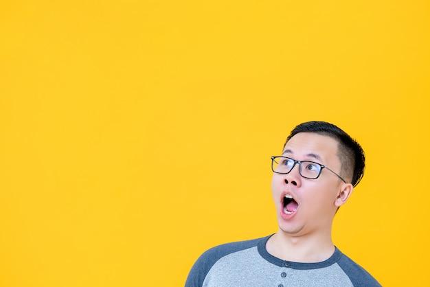 Zszokowany azjatycki mężczyzna z trudem łapie powietrze i chce skopiować na bok przestrzeń
