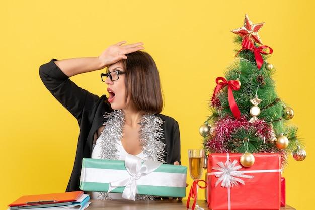 Zszokowany biznes dama w garniturze w okularach pokazujący jej prezent i siedząc przy stole z drzewem xsmas na nim w biurze