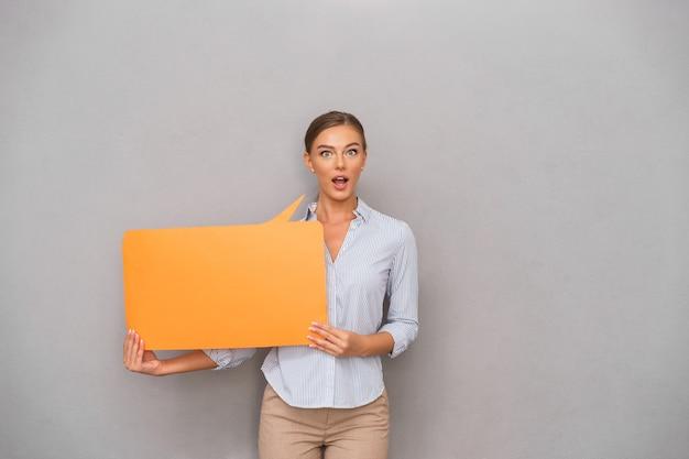 Zszokowany biznes kobieta stojąc na tle szarej ścianie trzymając dymek.