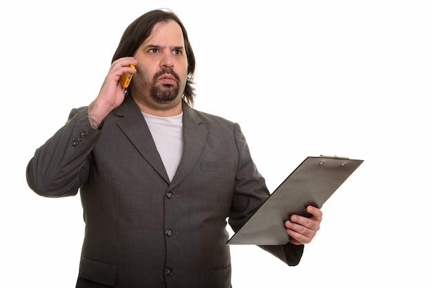 Zszokowany biznesmen tłuszczu kaukaski rozmawia przez telefon i trzymając schowek podczas myślenia