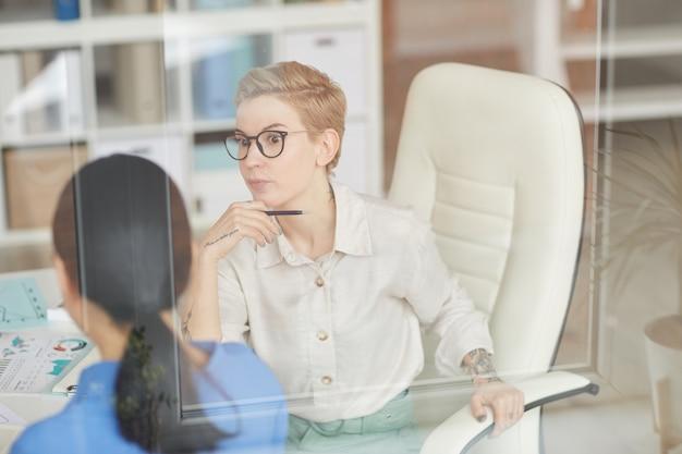 Zszokowany bizneswoman rozmawia z kolegą w biurze, kopia przestrzeń