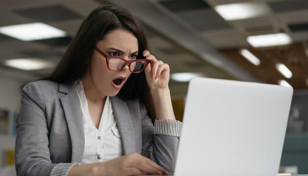 Zszokowany bizneswoman za pomocą laptopa, patrząc na ekran cyfrowy, oglądając najświeższe informacje
