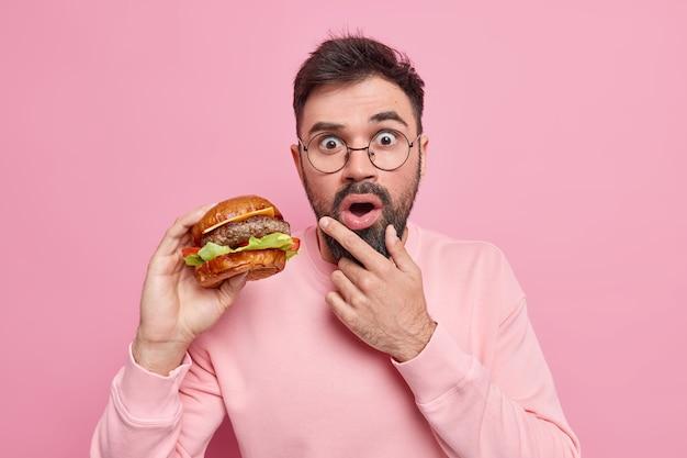 Zszokowany brodaty dorosły mężczyzna trzyma pyszny hamburger zjada fast food ma niezdrowe odżywianie trzyma podbródek ubrany w swobodny sweter