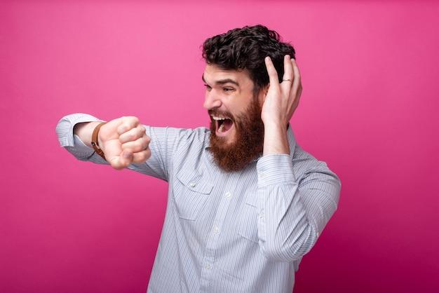 Zszokowany brodaty mężczyzna w swobodnym spojrzeniu na inteligentny zegarek