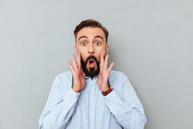 Zszokowany brodaty mężczyzna w ubrania biznesowe, trzymając ręce w pobliżu twarzy