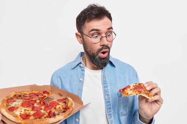 Zszokowany brodaty mężczyzna wpatruje się w kawałek pizzy, je fast food, nosi okrągłe okulary, a zwykła koszula ma dobry apetyt, będąc bardzo głodnym, pozuje w pomieszczeniu przy białej ścianie. dostawa usługi