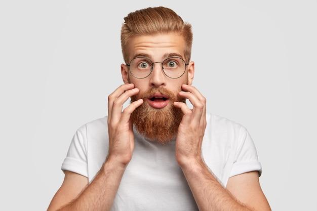 Zszokowany, brodaty rudowłosy mężczyzna patrzy ze zdumieniem prosto w kamerę, trzyma ręce przy policzkach