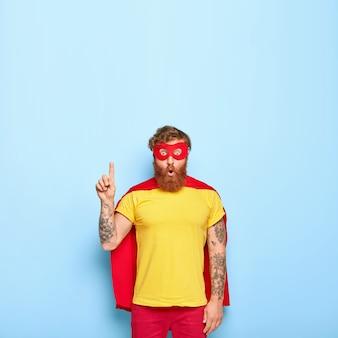 Zszokowany, brodaty rudy mężczyzna superbohater ma wielką odwagę, ubrany w żółtą koszulkę