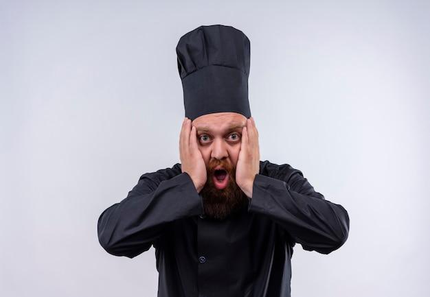 Zszokowany brodaty szef kuchni w czarnym mundurze, trzymając ręce na twarzy na białej ścianie