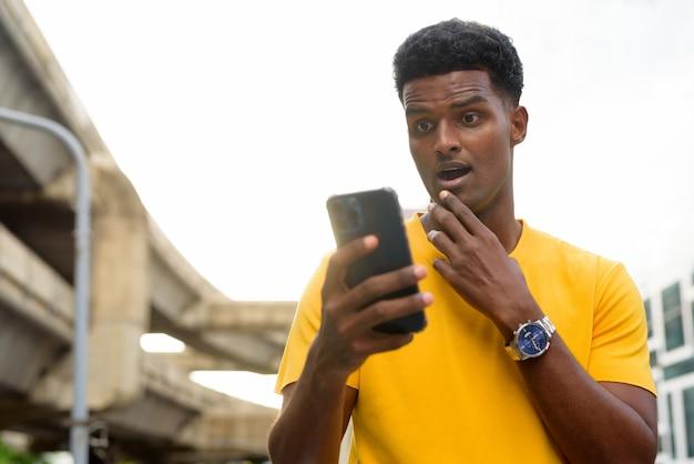 Zszokowany czarny afrykanin ubrany w żółtą koszulkę na zewnątrz w mieście latem podczas korzystania z telefonu komórkowego mobile