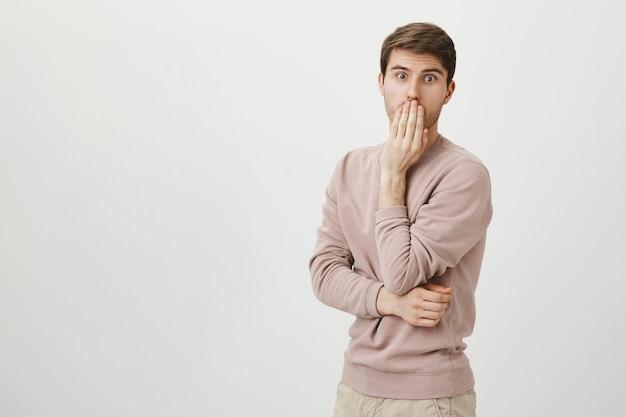 Zszokowany człowiek pod wrażeniem sapie i zakrywa usta, gapi się
