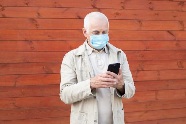Zszokowany dojrzały mężczyzna z medyczną maską twarzową, używając telefonu do wyszukiwania wiadomości