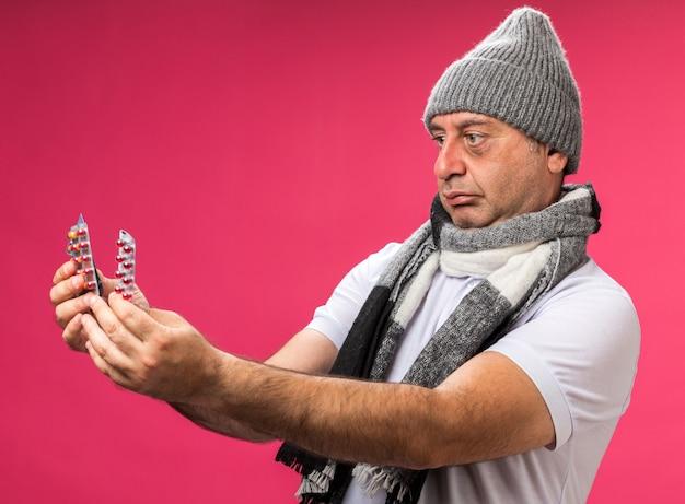 Zszokowany dorosły chory kaukaski mężczyzna z szalikiem na szyi w czapce zimowej trzymający i patrząc na różne opakowania leków na różowej ścianie z miejscem na kopię