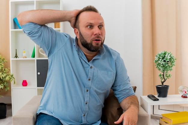 Zszokowany dorosły słowiański mężczyzna siedzi na fotelu, kładąc dłoń na głowie z tyłu, patrząc z boku w salonie