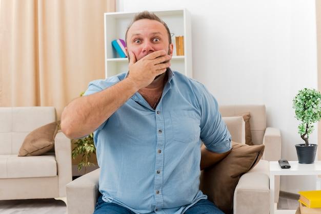 Zszokowany dorosły słowiański mężczyzna siedzi na fotelu, kładąc dłoń na ustach i trzymającą rękę od tyłu wewnątrz salonu