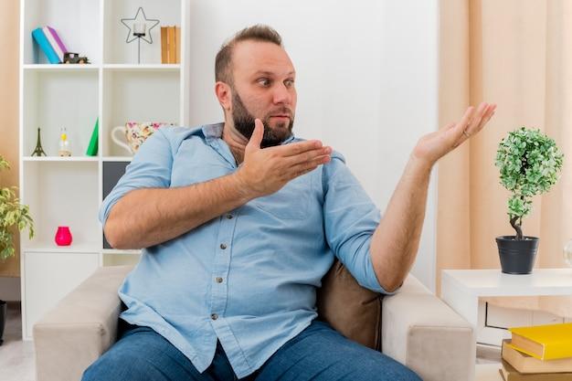 Zszokowany dorosły słowiański mężczyzna siedzi na fotelu, patrząc i wskazując na bok dwiema rękami w salonie