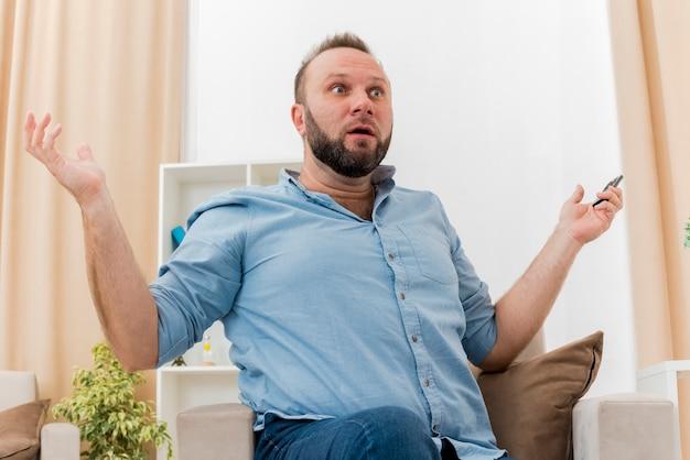 Zszokowany dorosły słowiański mężczyzna siedzi w salonie na fotelu trzymając pilota do telewizora z otwartymi rękami