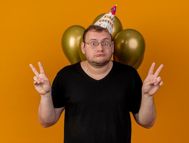 Zszokowany dorosły słowiański mężczyzna w okularach optycznych w czapce urodzinowej stoi przed balonami z helem, gestykulując ręką znak zwycięstwa dwiema rękami