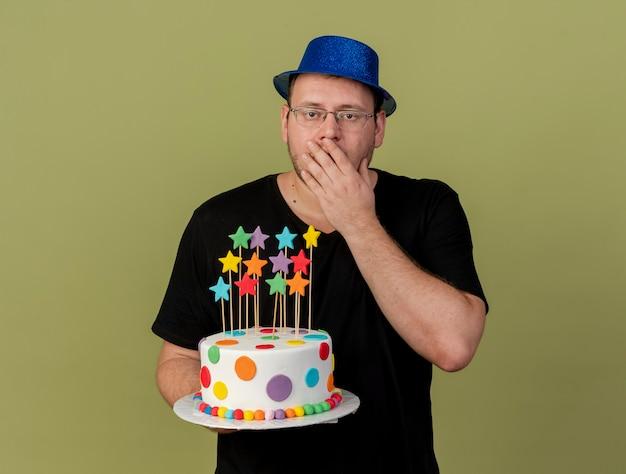 Zszokowany dorosły słowiański mężczyzna w okularach optycznych w niebieskiej imprezowej czapce kładzie rękę na ustach i trzyma tort urodzinowy