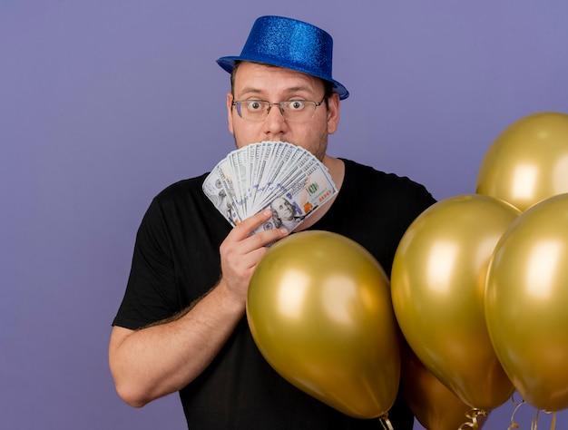 Zszokowany dorosły słowiański mężczyzna w okularach optycznych w niebieskim kapeluszu imprezowym stoi z balonami z helem trzymającymi pieniądze