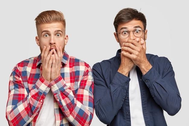 Zszokowany dwóch facetów sapie ze strachu, zakrywa usta obiema rękami, zdumiony strasznym wydarzeniem