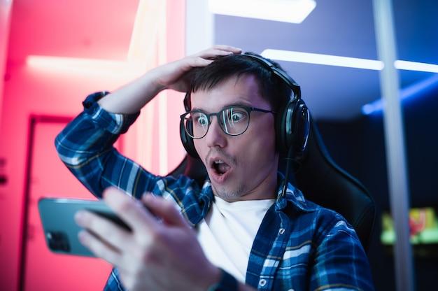 Zszokowany, ekspresyjny młody gracz w zestawie słuchawkowym z mikrofonem, który trzyma usta otwarte podczas patrzenia na ekran.