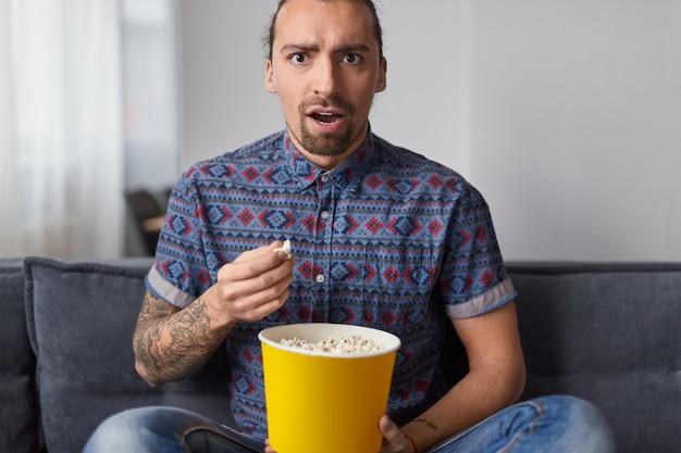 Zszokowany facet je popcorn i ogląda film