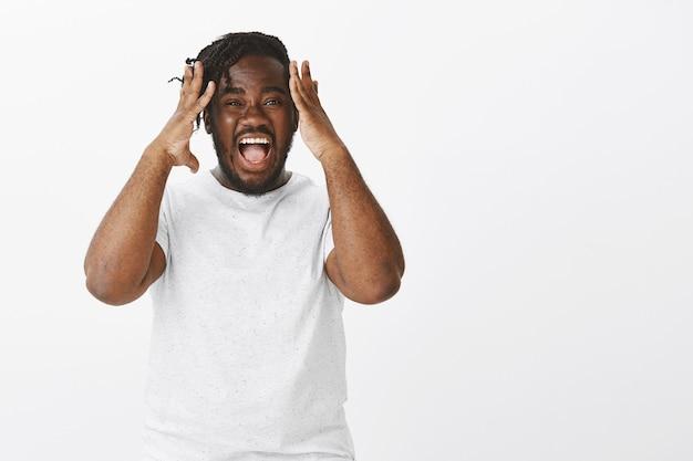 Zszokowany facet z warkoczami pozujący przy białej ścianie