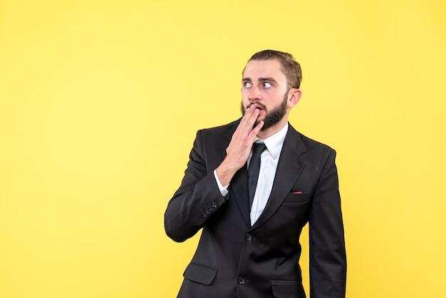 Zszokowany facet zamykający usta palcami