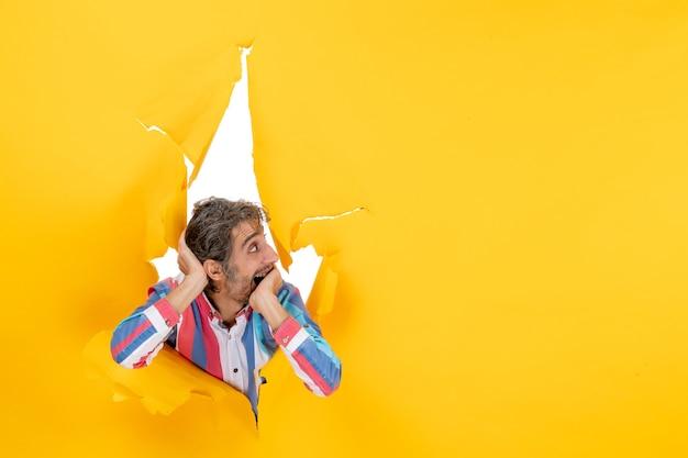 Zszokowany i emocjonalny młody człowiek patrzący na coś po lewej stronie w rozdartym żółtym tle dziury w papierze
