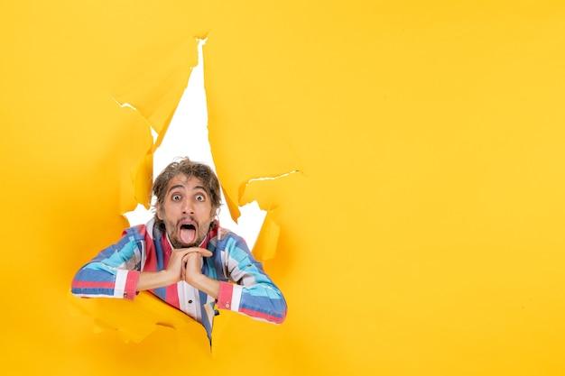 Zszokowany i emocjonalny młody człowiek w podartym żółtym tle dziury w papierze