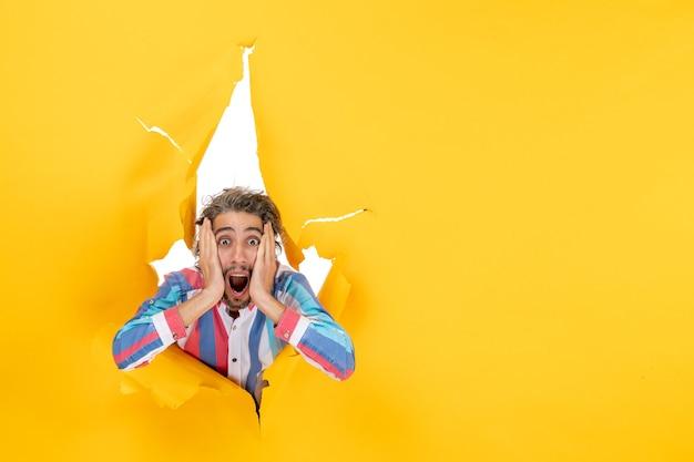 Zszokowany i emocjonalny młody facet pozuje do kamery przez rozdartą dziurę w żółtym papierze