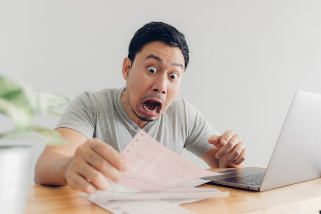 Zszokowany i zaskoczony mężczyzna ma problemy z rachunkami i długami.
