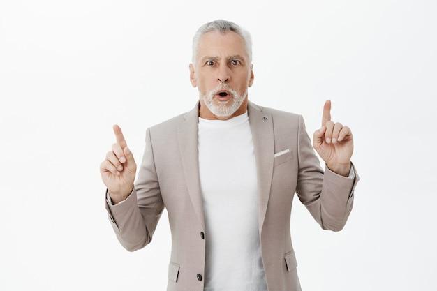 Zszokowany i zdumiony przystojny brodaty mężczyzna wskazujący palcami w górę, pokazujący reklamę