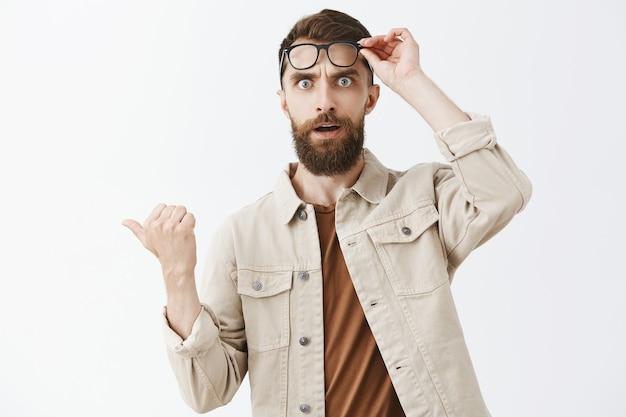 Zszokowany i zdziwiony brodaty mężczyzna w okularach pozuje pod białą ścianą